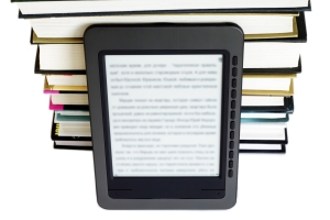 Ebook reader on pile of ordinary books