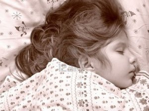 3823635-little-girl-sleeping-in-the-bed-sepia-toned