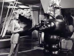"The one female in the movie (not the buxom long-haired blonde draped inn the evil robot's clutches), is asking the robot to sew her up a new dress so she look ""proper"" for the ship captain should she see him in the morning. The robot asks what kind of fabric she wants. Nothing threatening there."